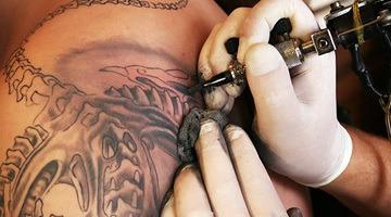 Мастер тату-салона делает тату
